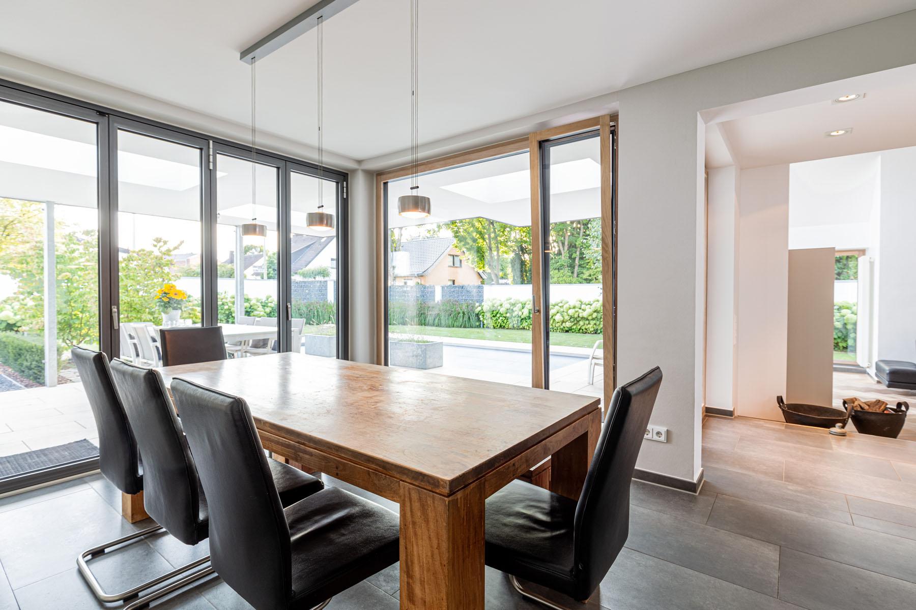 Essbereich mit Tisch und Stühlen und großen Holz und Alufenstern über die gesamte Breite