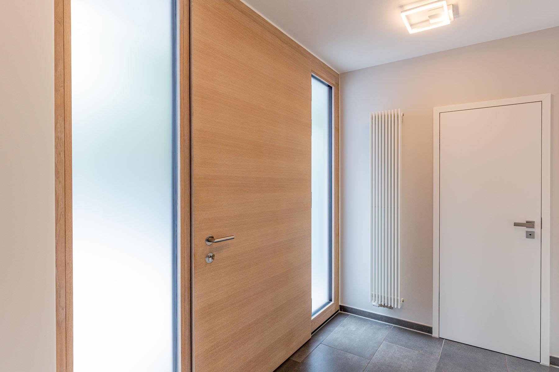 Flur mit Wohnungstür aus Holz und hellem Flurlicht