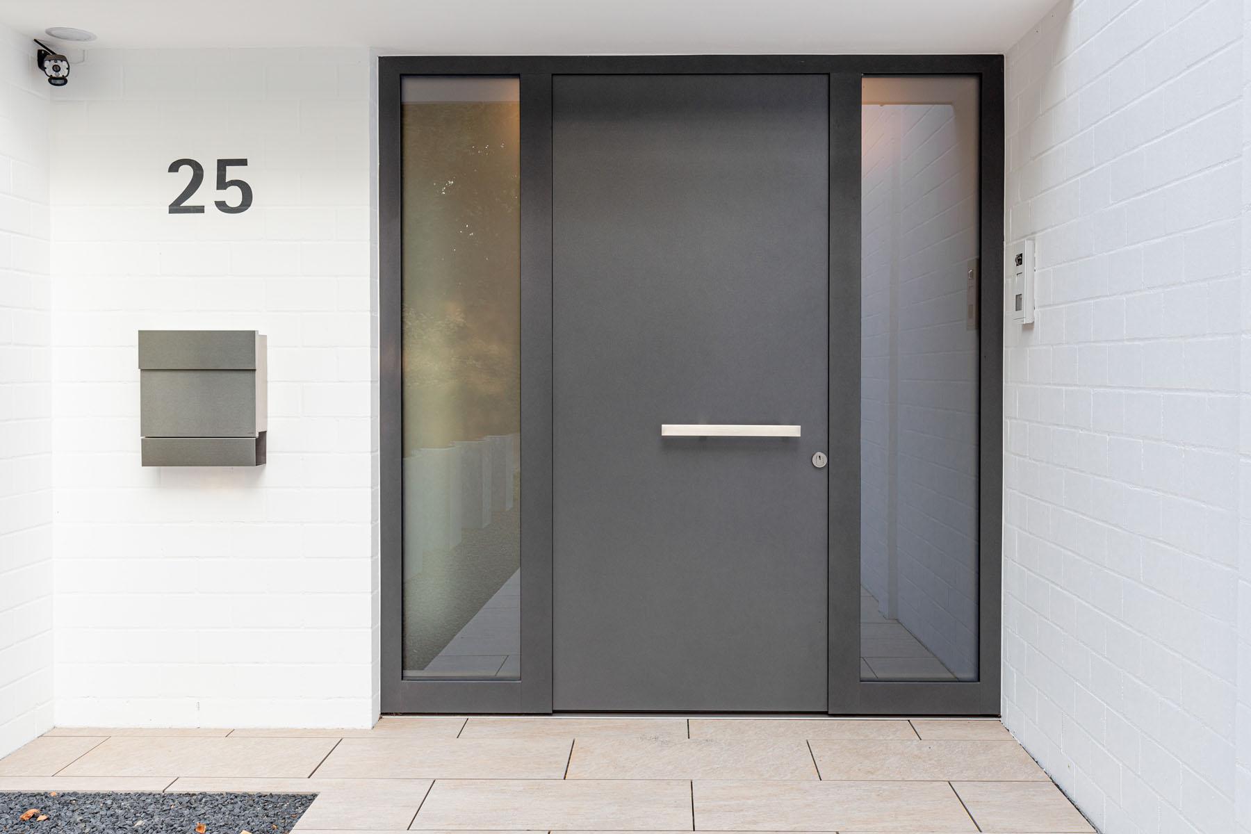 Haustür in grau mit Glaselementen rechts und links