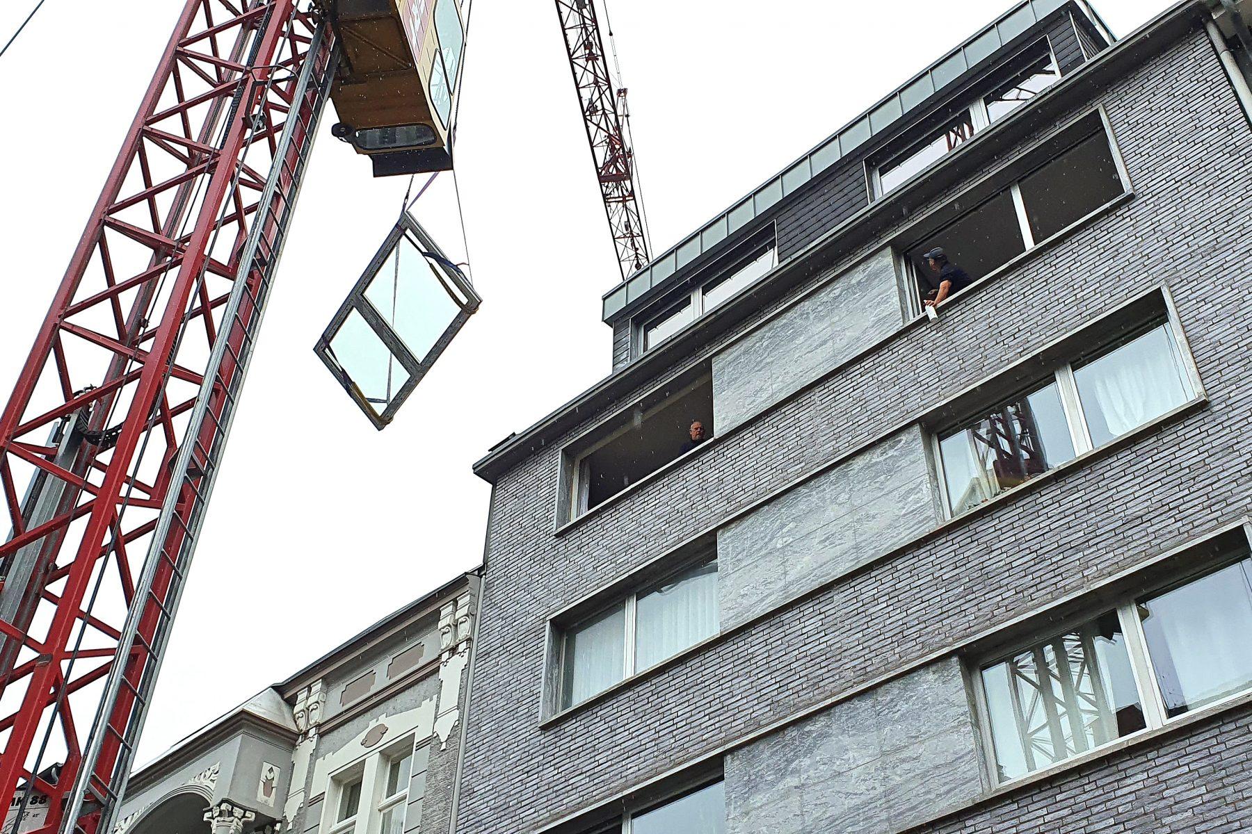 Kran hebt Fensterelement in den oberen Stock eines Hauses